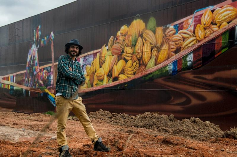 Brazilian mural artist Eduardo Kobra poses in front of his recent work -the biggest mural in the world with 5,742 square meters- in Itapevi, metropolitan area of Sao Paulo, Brazil on April 12, 2017 (AFP Photo/NELSON ALMEIDA)