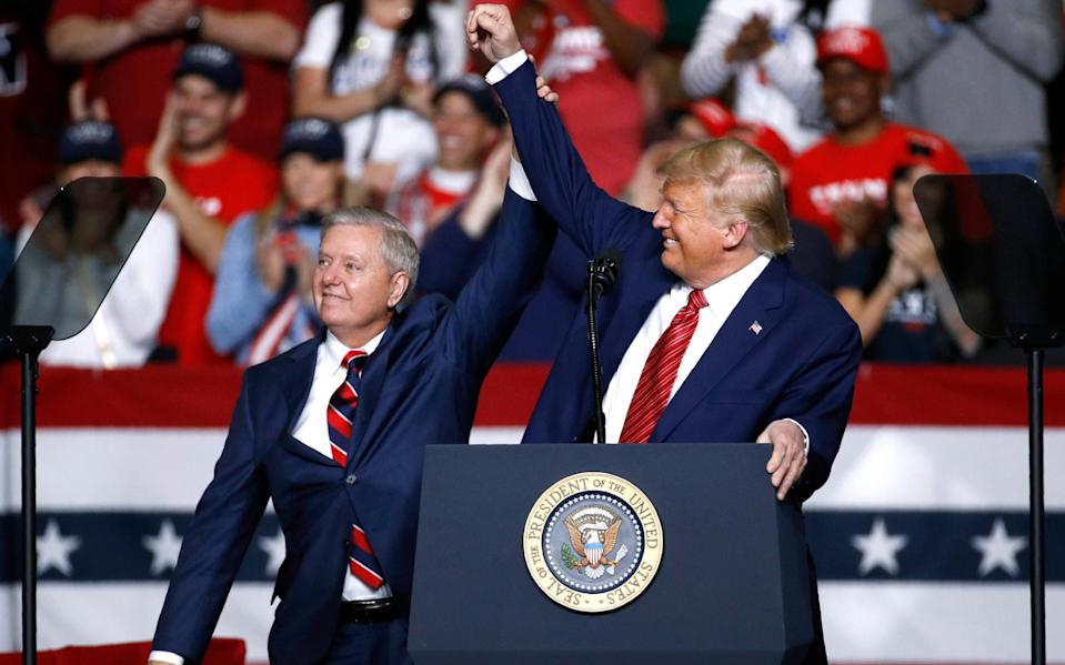 Sen. Lindsey Graham stands onstage with President Donald Trump during a Feb. 28 campaign rally in North Charleston, South Carolina - AP