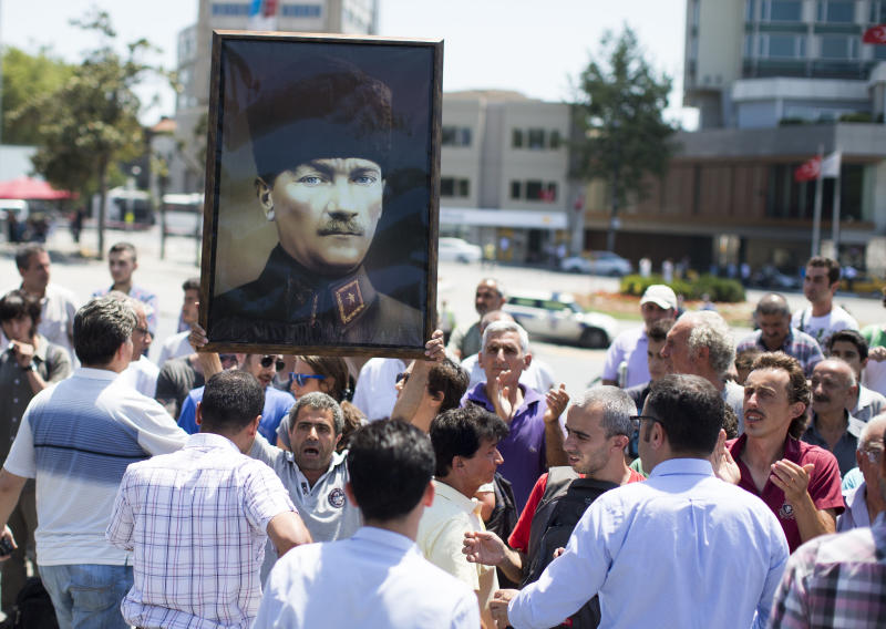 A man holds a giant poster showing Mustafa Kemal Ataturk as he waits to enter Gezi park at Taksim Square in Istanbul, Turkey, Monday, July 8, 2013. Istanbul's governor re-opened the park that was at the center of weeks of anti-government protests but warned he would not allow it to become a point for more demonstrations or occupation. (AP Photo/Gero Breloer)