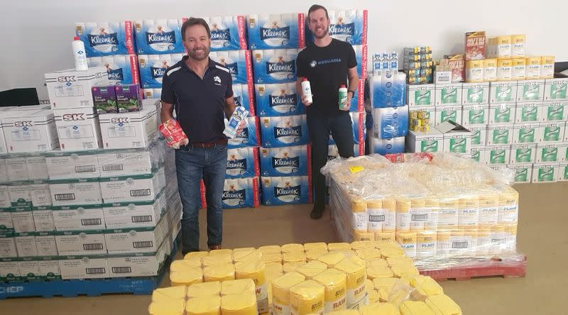 Heath Nelson of Fortescue Metals Group and Chris Schmid of Woollahra Group pose by goods, which are ready to be packed and delivered to help remote Aboriginal communities, in Perth