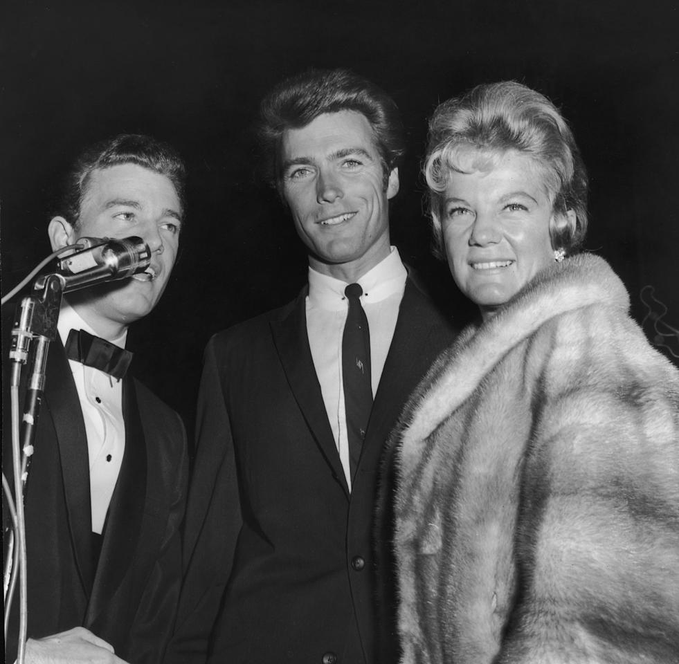 <p>Clint Eastwood and his first wife, Maggie, pose next to an announcer at the West Coast premiere of <em>Breakfast at Tiffany's</em> in 1961. </p>