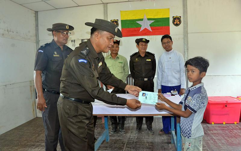 Myanmar immigration official (2nd L) handing over identification documents to an unidentified Rohingya boy - AFP