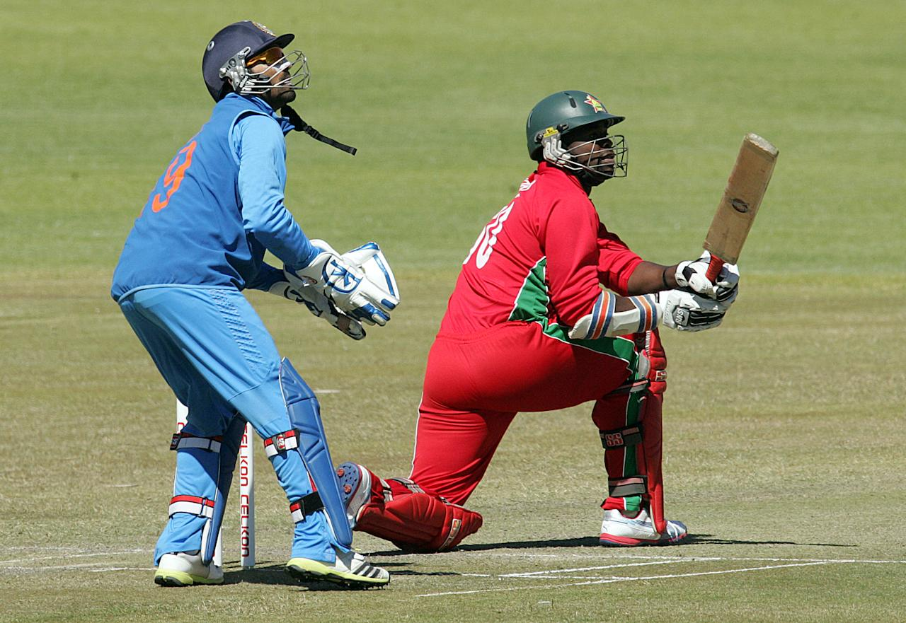 Zimbabwe batsman Brian Vitori hits a big six as India wicket keeper Dinesh Kharthik looks on during the 4th match of the 5-match cricket ODI series between Zimbabwe and India at Queen's Sports Club in Harare on August 1, 2013. AFP PHOTO / Jekesai Njikizana        (Photo credit should read JEKESAI NJIKIZANA/AFP/Getty Images)