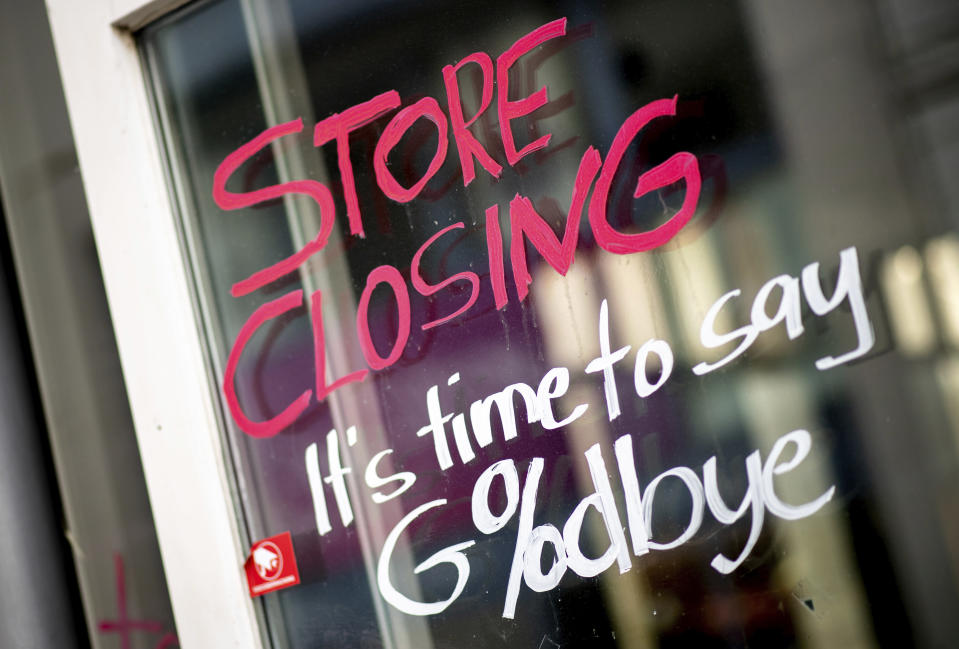 """The words """"Store Closing"""" and the addition """"It's time to say Goodbye"""" with a percent sign are written on the window of a closed store in the city center in Oldenburg, Germany, Thursday, April 1, 2021. In view of sharply rising Corona infection figures, the German government has extended the lockdown in Germany until April 18, 2021. (Hauke-Christian Dittrich/dpa via AP)"""