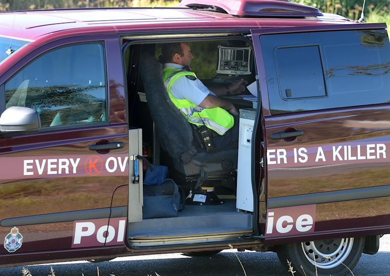 A police officer operates a mobile speed camera from the back of a van on the Pacific Highway on the Gold Coast.