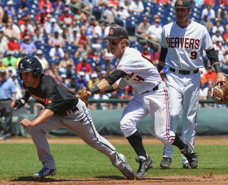 Louisville's Cole Sturgeon, left, is tagged out by Oregon State second basemen Andy Peterson during a run down between first and second bases in the first inning of an NCAA College World Series game in Omaha, Neb., Monday, June 17, 2013. At right is Oregon State first baseman Danny Hayes. (AP Photo/Ted Kirk)