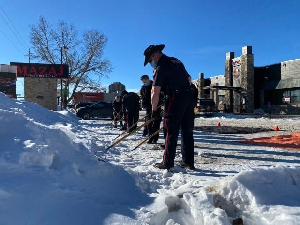 Calgary police search for evidence in a snow bank near the Mazaj Lounge and Restaurant on Saturday morning.