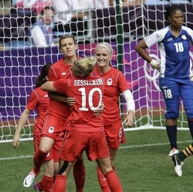 Canada's Christine Sinclair, center, is hugged by her teammate Lauren Sesselmann, after scoring during the group F women's soccer match between South Africa and Canada at the London 2012 Summer Olympics, in Coventry, England, Saturday, July 28, 2012. (AP Photo/Hussein Malla)