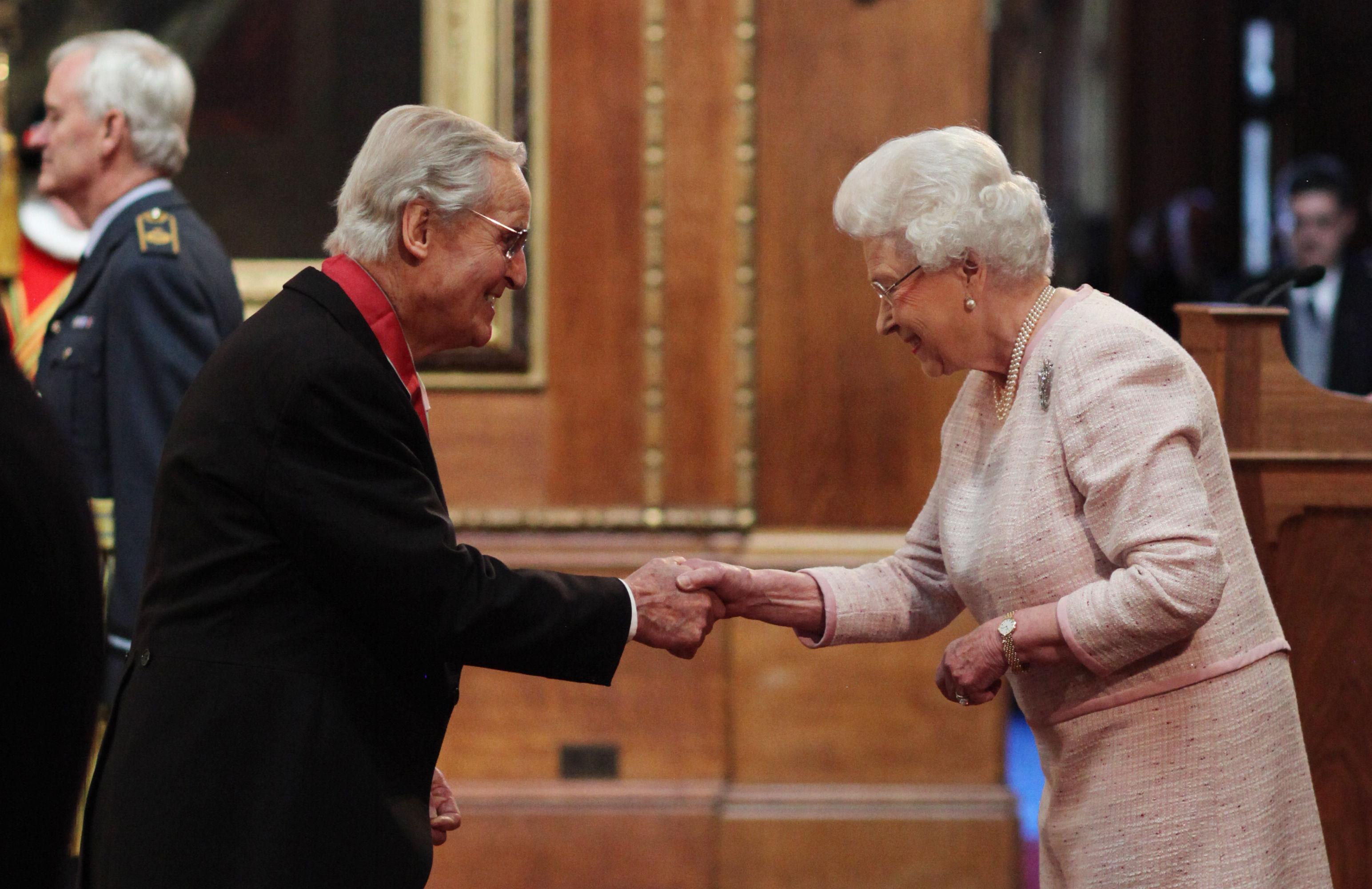 Entertainer Nicholas Parsons is made a Commander of the Order of the British Empire (CBE) by Queen Elizabeth II during an Investiture ceremony at Windsor Castle, Berkshire.