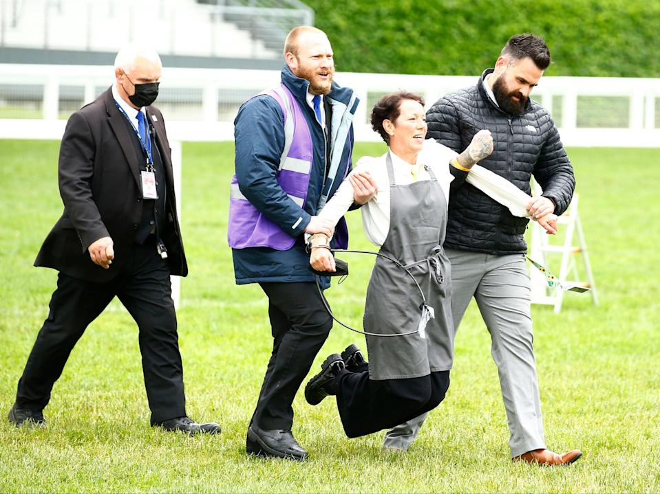 An XR protestor is escorted from the racecourse during the races (Action Images via Reuters)