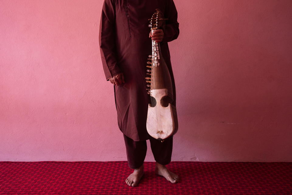An Afghan musician poses for a portrait with his rubab in Kabul, Afghanistan, Thursday, Sept. 16, 2021. About a month after the Taliban seized power in Afghanistan, the music is starting to go quiet. The last time that the militant group ruled the country, in the late 1990s, it outright banned music. (AP Photo/Bernat Armangue)