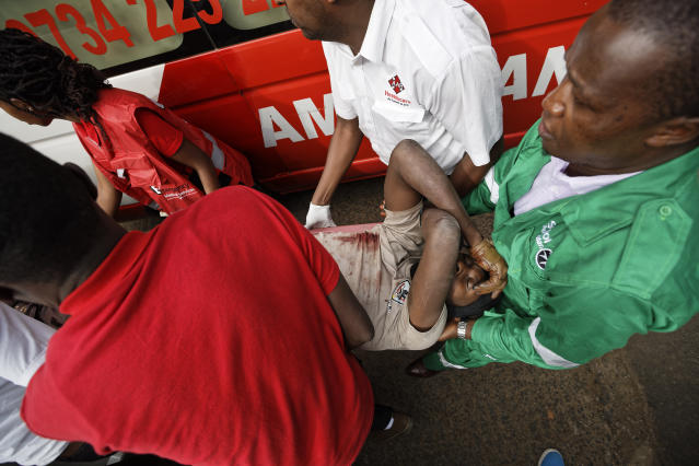 A wounded member of Kenyan special forces is carried from a US embassy diplomatic vehicle into an ambulance by paramedics at the scene Wednesday, Jan. 16, 2019 in Nairobi, Kenya. Extremists stormed a luxury hotel in Kenya's capital on Tuesday, setting off thunderous explosions and gunning down people at cafe tables in an attack claimed by Africa's deadliest Islamic militant group. (AP Photo/Ben Curtis)