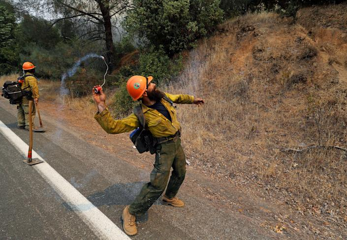 A firefighter throws an incendiary device into the brush to ignite backfires while battling the Ranch Fire north of Upper Lake, California.