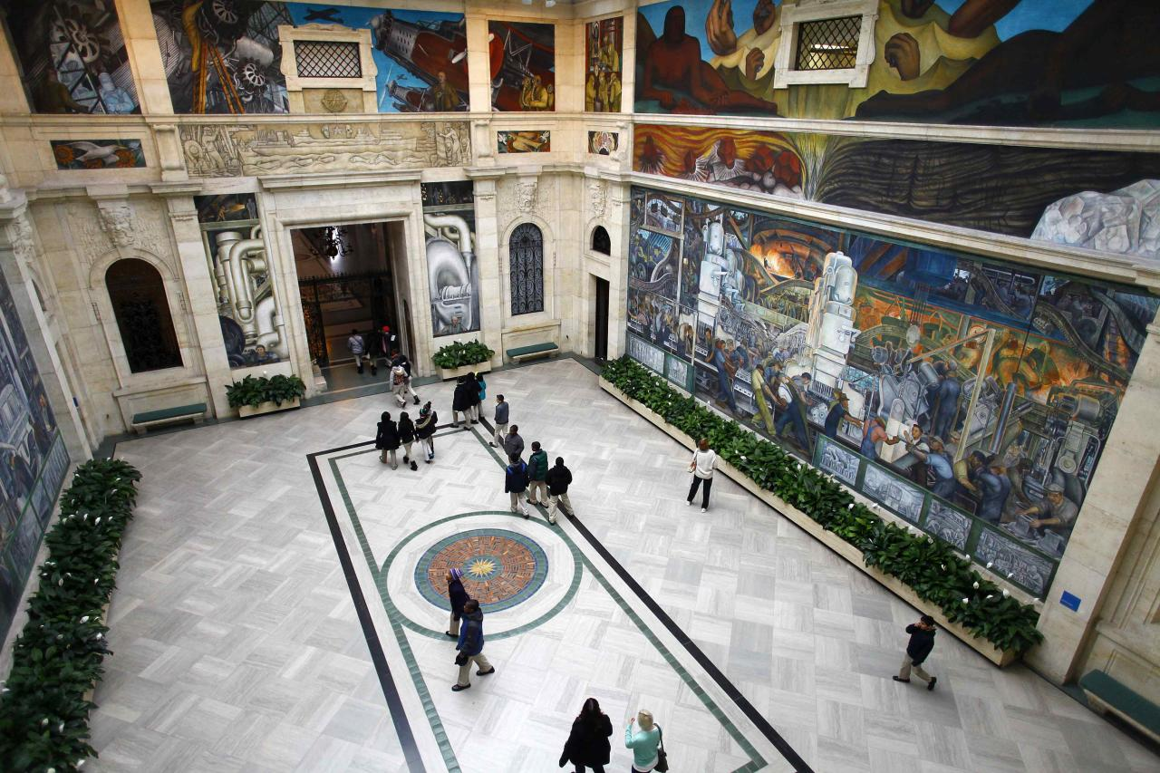 People look at a mural by artist Diego Rivera at the Art Institute of Detroit in Detroit, Michigan December 3, 2013. Some of the art collection owned by the city of Detroit is in jeopardy of being auctioned off due to the city's current financial situation. Detroit is eligible for the biggest municipal bankruptcy in U.S. history because the city is broke and negotiations with its thousands of creditors were unfeasible, a federal judge said on Tuesday in a wide-ranging ruling that also said the city could cut retiree pensions. REUTERS/Joshua Lott (UNITED STATES - Tags: CRIME LAW BUSINESS POLITICS)