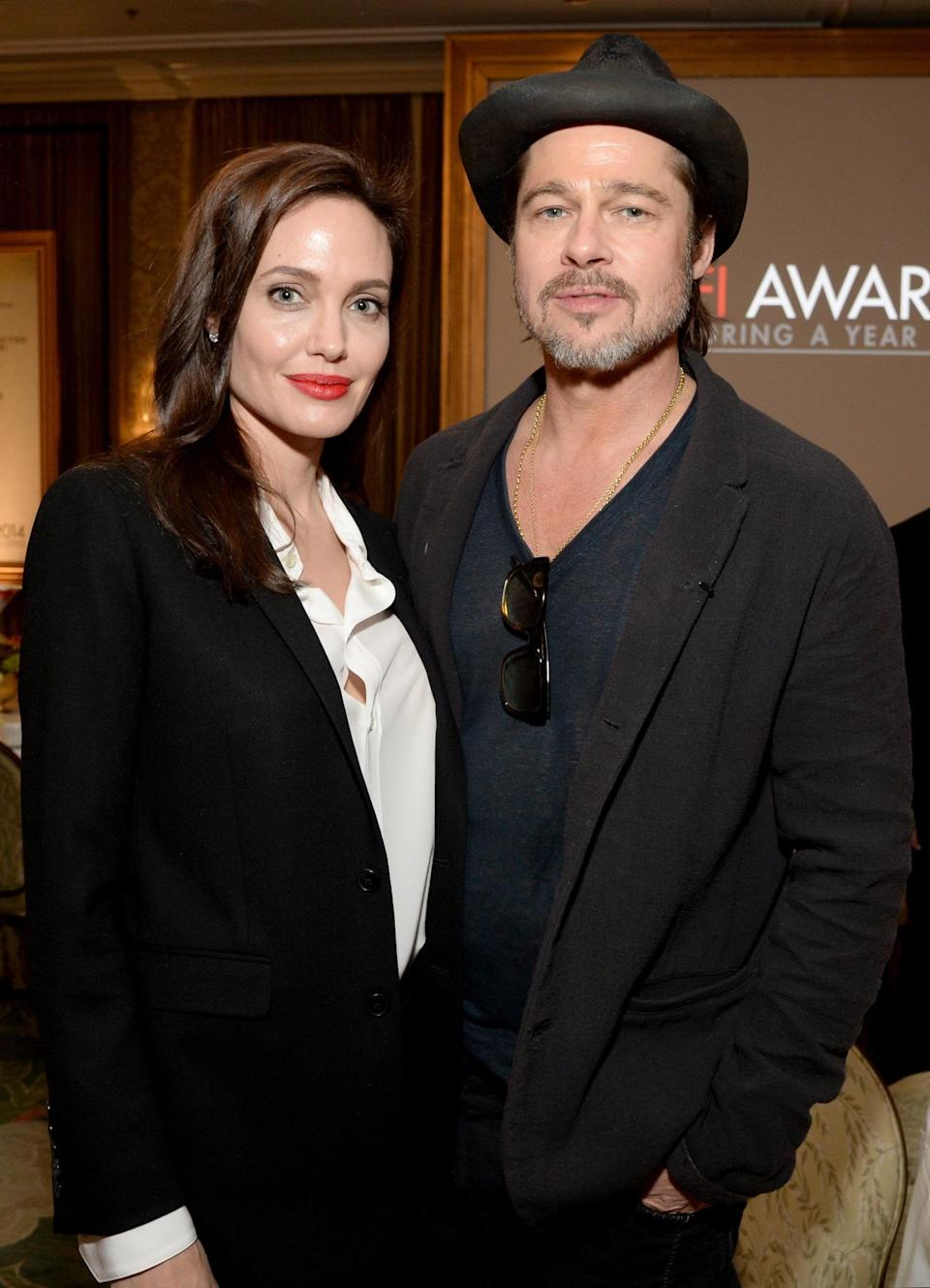 "Brad Pitt, who was also honored at the lunch for his work with ""Selma,"" stood by his wife's side in casual sheer tea, dark jeans, blazer, and hat."