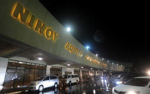 Vehicles pass the facade of the Manila International Airport