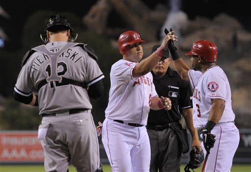 Los Angeles Angels' Kendrys Morales, center, center is congratulated by Alberto Callaspo as Chicago White Sox catcher A.J. Pierzynski looks on after hitting a solo home run during the second inning of their baseball game, Friday, Sept. 21, 2012, in Anaheim, Calif. AP Photo/Mark J. Terrill)