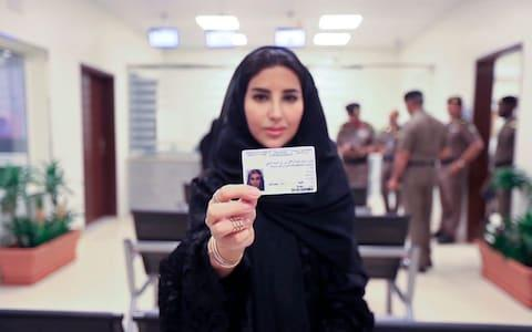 A Saudi woman displays her new driving license, at the General Department of Traffic in the capital, Riyadh, after the kingdom lifts the ban on women driving in June last year - Credit: AP