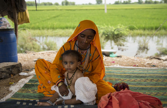 Rihanna clothes her son Rehan after bathing him with rainwater on the side of the road, where many like her are camping after their homes were devastatedSaiyna Bashir/Arete/WFP