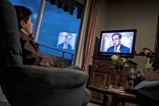 People watch on TV the televised national debate between Francois Hollande and Nicolas Sarkozy at their home in Meyzieu