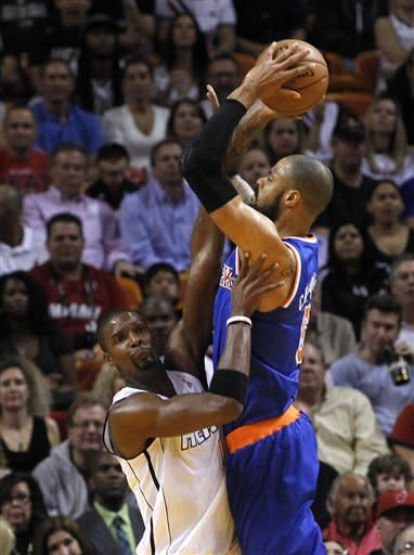 New York Knicks' Tyson Chandler, right, prepares to shoot over Miami Heat's Chris Bosh (1) in the first half of an NBA basketball game, Thursday, Dec, 6, 2012, in Miami. ( AP Photo/Alan Diaz)