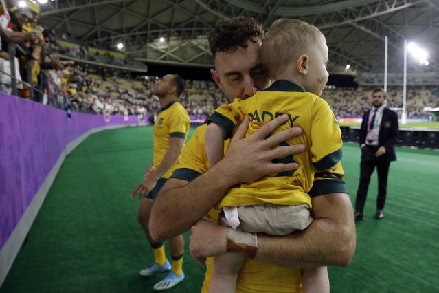 Australia's Nic White kisses his son after the Rugby World Cup quarterfinal match at Oita Stadium between England and Australia in Oita, Japan, Saturday, Oct. 19, 2019. England won 40-16. (AP Photo/Aaron Favila)