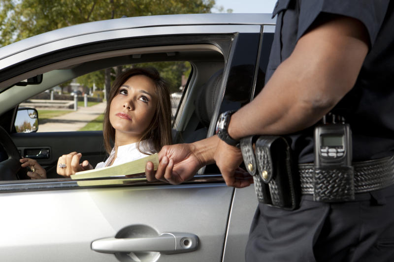 A woman sitting in car receives a road rule violation ticket from police officer.