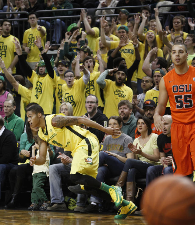 As Oregon's Joseph Young scrambles down court, left, Duck fans cheer as his 3-point shot falls and Oregon State's Roberto Nelson waits to inbound the ball during the first half of an NCAA college basketball game in Eugene, Ore., Sunday, Feb. 16, 2014. (AP Photo/Chris Pietsch)