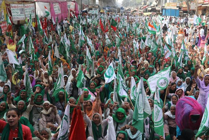 Crowd of hundreds of women holding green flags and raising their fists in the streets