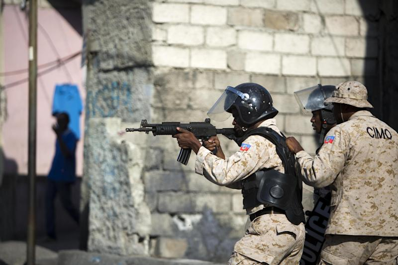A national police officer points his gun at supporters of presidential candidate Maryse Narcisse protesting final election results in Port-au-Prince, Haiti, Tuesday, Jan. 3, 2017. An electoral tribunal certified the presidential election victory of first-time candidate Jovenel Moise. (AP Photo/Dieu Nalio Chery)
