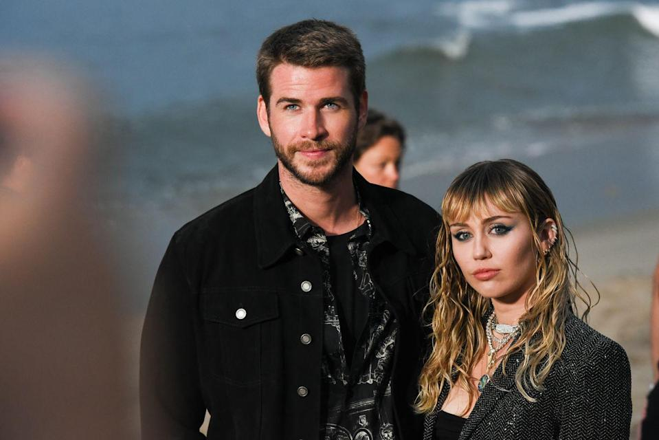 """<p>In July 2019, Cyrus gave some revealing quotes to <a href=""""https://www.elle.com/culture/music/a28280119/miley-cyrus-elle-interview/"""" rel=""""nofollow noopener"""" target=""""_blank"""" data-ylk=""""slk:ELLE"""" class=""""link rapid-noclick-resp"""">ELLE</a> about her """"modern"""" marriage. """"I think it's very confusing to people that I'm married. But my relationship is unique. And I don't know that I would ever publicly allow people in there because it's so complex, and modern, and new that I don't think we're in a place where people would get it,"""" she said, later adding, """"I definitely don't fit into a stereotypical wife role. I don't even like that word."""" On August 10, Cyrus's rep confirmed the couple was splitting in a statement to <em><a href=""""https://people.com/music/miley-cyrus-liam-hemsworth-split/"""" rel=""""nofollow noopener"""" target=""""_blank"""" data-ylk=""""slk:People"""" class=""""link rapid-noclick-resp"""">People</a>. </em>The confirmation arrived after Cyrus was <a href=""""https://www.etonline.com/miley-cyrus-spotted-kissing-brody-jenners-ex-kaitlynn-carter-in-italy-see-the-pda-packed-pics"""" rel=""""nofollow noopener"""" target=""""_blank"""" data-ylk=""""slk:spotted kissing Kaitlynn Carter"""" class=""""link rapid-noclick-resp"""">spotted kissing Kaitlynn Carter</a>. Their divorce was finalized in <a href=""""https://www.elle.com/culture/celebrities/a30692789/miley-cyrus-liam-hemsworth-divorce-finalized/"""" rel=""""nofollow noopener"""" target=""""_blank"""" data-ylk=""""slk:January 2020"""" class=""""link rapid-noclick-resp"""">January 2020</a> and Cyrus has since written songs """"Slide Away"""" and """"Midnight Sky"""" about their breakup.</p>"""