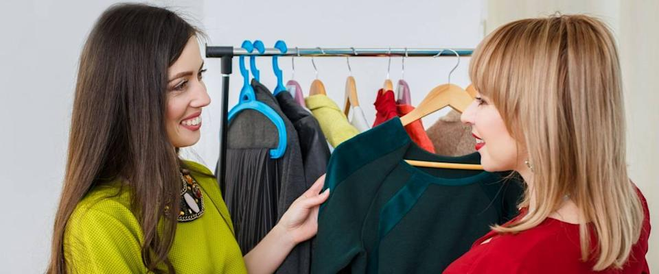 girl with stylist choosing her fashion outfit. Women deciding what to wear. Analysis of the client's wardrobe. Fashion stylist consultation. Master class about how to stylishly clothing