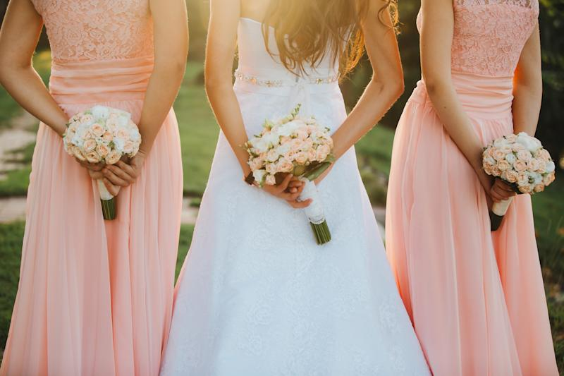 The bride and bridesmaids in an elegant dress is standing and holding hand bouquets of pastel pink flowers and greens with ribbon at nature. Young beautiful girls holds a wedding bouquet outdoors.