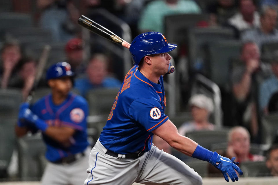 New York Mets' James McCann follows through on an RBI-double in the seventh inning of a baseball game against the Atlanta Braves, Monday, May 17, 2021, in Atlanta. (AP Photo/John Bazemore)