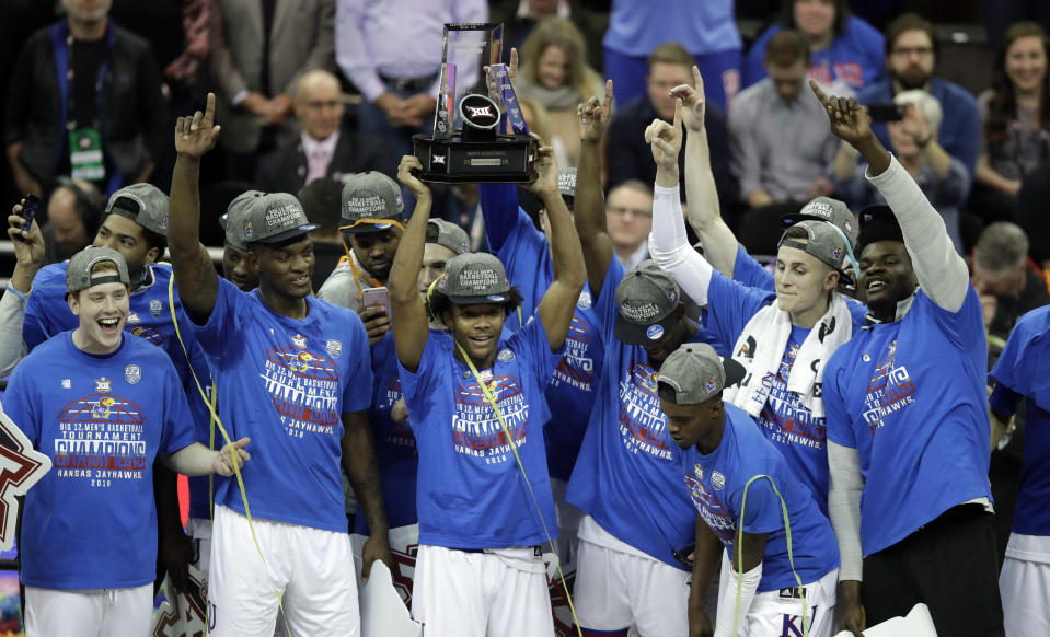 Kansas players celebrate as the Big 12 conference championship trophy is help by Devonte' Graham following the Jayhawks' victory on Saturday against West Virginia. (AP)