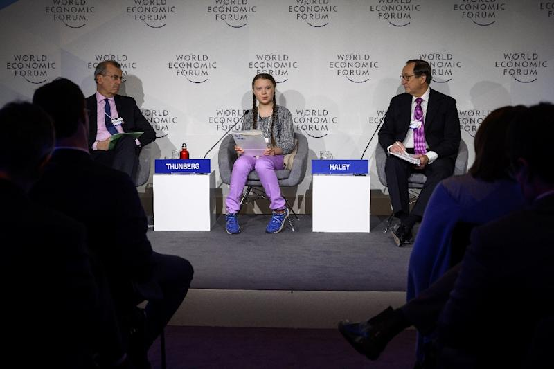 Swedish youth climate activist Greta Thunberg (C) delivers a speech between Governor of the Bank of France Francois Villeroy de Galhau (L) and Willis Towers Watson CEO John Haley during the closing day of the World Economic Forum (WEF) in Davos (AFP Photo/Fabrice COFFRINI)