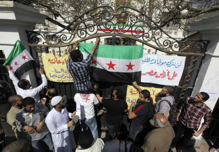 """Dozens of mostly ultraconservative Muslim protesters shout anti-Iran slogans and hang a Syrian revolution flag outside the residence of Iran's top diplomat to protest the Egyptian government's attempt to improve ties with Tehran in Cairo, Egypt, Friday, April 5, 2013. An Iranian flag seen at background. Arabic on banner reads """"we will not let Shiites step in Egypt."""" (AP Photo/Amr Nabil)"""
