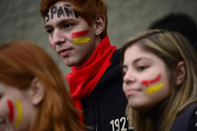 Soccer fans, whose faces are painted with the colors of Spain's national soccer team, wait to enter the Atletico Paranaense training center to watch Spain's practice session, in Curitiba, Brazil, Tuesday, June 10, 2014. Spain will play in group B of the Brazil 2014 soccer World Cup. (AP Photo/Manu Fernandez)