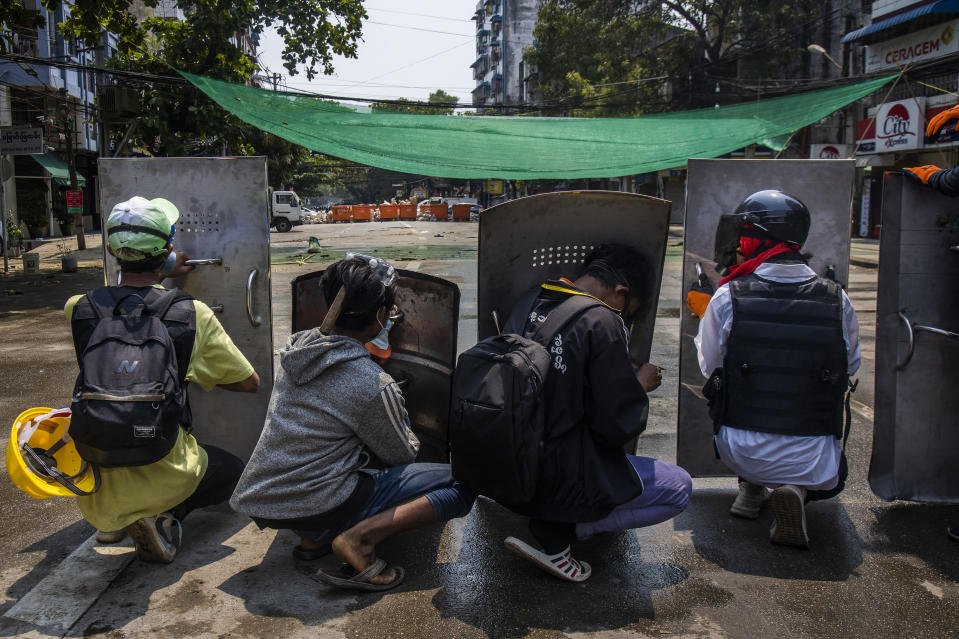 Anti-coup protesters take positions behind makeshift barricades as riot policemen arrive in Yangon, Myanmar, Friday, March 12, 2021. Myanmar's security forces shot to death at least 10 people protesting the military's coup, spurning a U.N. Security Council appeal to stop using lethal force. (AP Photo)