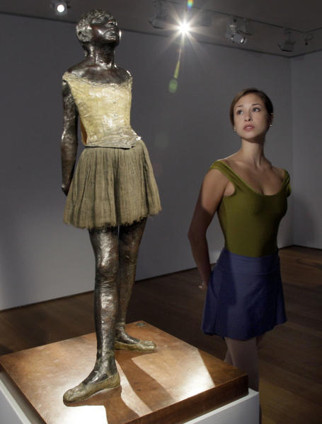 "FILE - In a Tuesday, Oct. 25, 2011 file photo, Puanani Brown, a member of the corps de ballet of the American Ballet Theatre, poses with Edgar Degas ""Petite danseuse de quatorze ans,"" at Christie's auction house, in New York.  The bronze sculpture failed to find a buyer at Christie's New York auction of impressionist and modern art Tuesday night, Nov. 1, 2011. The sculpture had a pre-sale estimate of $25 million to $35 million, but there were no bids.  (AP Photo/Richard Drew, File)"