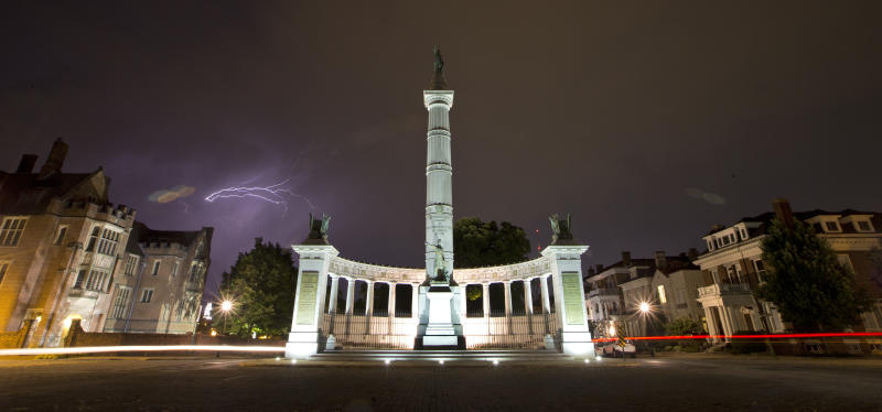 FILE - In this July 17, 2017 file photo, lightening streaks across the sky behind a statue honoring Confederate President Jefferson Davis on Monument Avenue in Richmond, Va. Virginia Democrats seized control of the General Assembly last week and that means Confederate statues could soon be coming down in a state that's full of them. (AP Photo/Steve Helber, File)