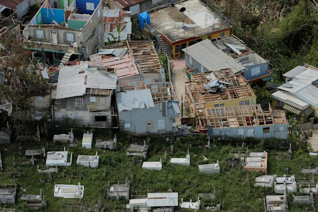<p>The remains of damaged homes stand next to a cemetery as recovery efforts continue following Hurricane Maria in Morovis, Puerto Rico, Oct. 7, 2017. (Photo: Lucas Jackson/Reuters) </p>