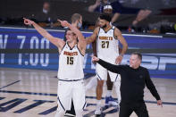 Denver Nuggets center Nikola Jokic (15) and Denver Nuggets head coach Michael Malone, right, celebrate their win over the Los Angeles Clippers in an NBA conference semifinal playoff basketball game Tuesday, Sept. 15, 2020, in Lake Buena Vista, Fla. (AP Photo/Mark J. Terrill)