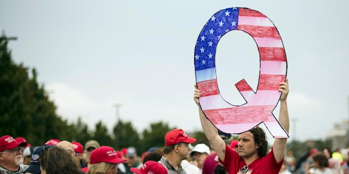 A man holding a Q sign waits in line with others to enter a campaign rally with President Donald Trump and U.S. Senate candidate Rep. Lou Barletta, R-Pa., Thursday, Aug. 2, 2018, in Wilkes-Barre, Pa.