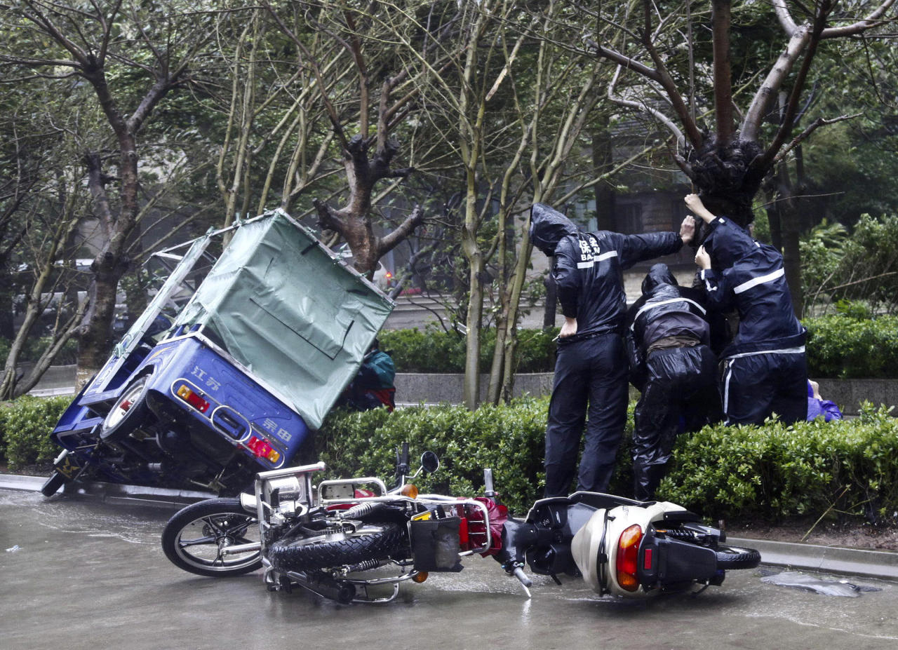 Motorcyclists hold on to a tree in strong winds as typhoon Nesat hits Haikou in south China's Hainan province, Thursday, Sept. 29, 2011. The powerful typhoon slammed into southern China on Thursday after skirting Hong Kong and bringing death and widespread flooding to the Philippines earlier this week (AP Photo) CHINA OUT