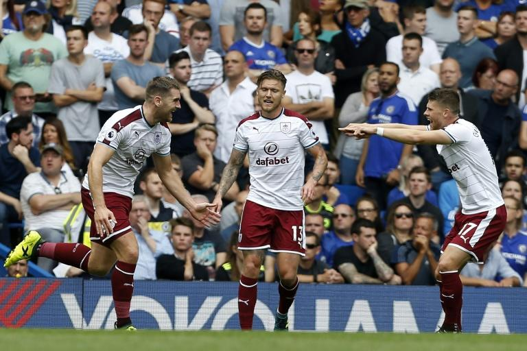 Burnley's Sam Vokes (L) celebrates with teammates, Jeff Hendrick (C) and Johann Berg Gudmundsson, after scoring the opening goal of their English Premier League match against Chelsea, at Stamford Bridge in London, on August 12, 2017
