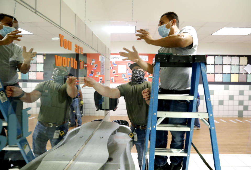 Richardson Independent School District workers Rogelio Ponciano, right, and Matt Attaway install a plexiglass barrier for the sink in the student restroom at Bukhair Elementary School in Dallas, Wednesday, July 15, 2020. Texas Education Commissioner Mike Morath told the state Board of Education on Tuesday that the annual State of Texas Assessments of Academic Readiness, also known as STAAR, will return in the 2020-2021 school year. (AP Photo/LM Otero)