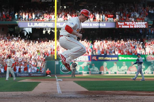 St. Louis Cardinals' David Freese jumps over home plate after scoring from third on a sacrifice fly by Jon Jay during the fifth inning of Game 2 of the National League baseball championship series against the Los Angeles Dodgers Saturday, Oct. 12, 2013, in St. Louis. (AP Photo/St. Louis Post-Dispatch, Chris Lee)