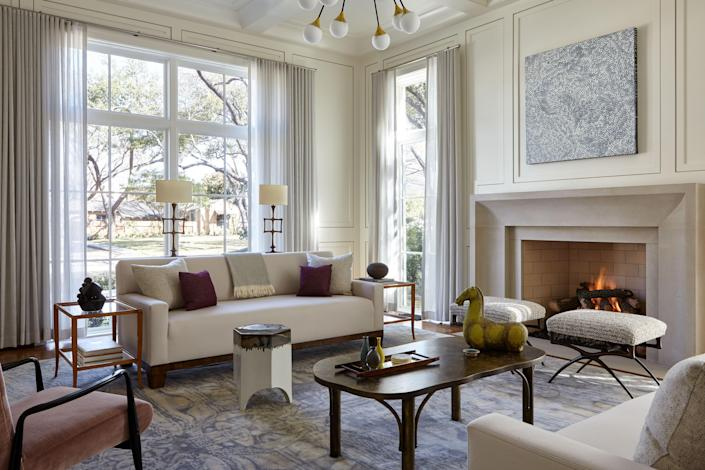 """The designer used one of the contemporary artworks in the couple's collection, a blue-gray abstract painting by Yayoi Kusama, as the living room's foundational piece. He then proceeded to mix and match various furnishings to fit the soothing palette of the space. A set of custom sofas made by <a href=""""http://www.interiorsbyjclanda.com/"""" rel=""""nofollow noopener"""" target=""""_blank"""" data-ylk=""""slk:J.C. Landa"""" class=""""link rapid-noclick-resp"""">J.C. Landa</a> and a vintage bronze coffee table by Philip and Kelvin LaVerne, which had been in the loft's main reception area, were paired with a Chinese silk rug from <a href=""""http://fortstreetstudio.com"""" rel=""""nofollow noopener"""" target=""""_blank"""" data-ylk=""""slk:Fort Street Studio"""" class=""""link rapid-noclick-resp"""">Fort Street Studio</a> and a pair of sculptural <a href=""""https://www.donzella.com/shop/2018/10/8/wide-version-atlante-sculptural-bronze-bench-by-alexandre-log"""" rel=""""nofollow noopener"""" target=""""_blank"""" data-ylk=""""slk:bronze-legged stools by Alexandre Logé"""" class=""""link rapid-noclick-resp"""">bronze-legged stools by Alexandre Logé</a>, which had been in the loft's den."""