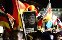 Supporters of the anti-Islamic PEGIDA movement hold a poster featuring German Chancellor Angela Merkel wearing a head scarf, during a 2015 rally in Dresden, eastern Germany (AFP Photo/Robert Michael)